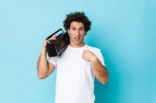 Jovem homem encaracolado, caucasiano, segurando um blaster guetto surpreso, apontando para si mesmo, sorrindo amplamente.