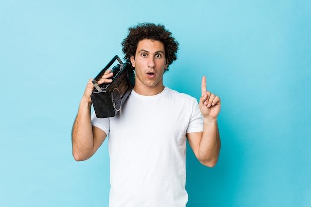 Jovem homem encaracolado caucasiano segurando um blaster guetto, tendo uma ótima ideia, o conceito de criatividade.