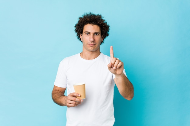 Jovem homem encaracolado caucasiano, segurando um café para viagem, mostrando o número um com o dedo.