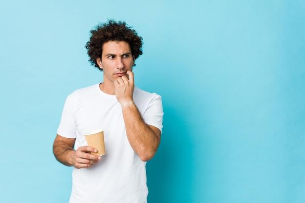 Jovem homem encaracolado caucasiano segurando um café para viagem relaxado pensando em algo olhando para um espaço de cópia.
