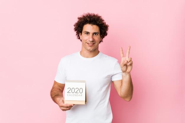 Jovem homem encaracolado caucasiano, segurando um calendário 2020, mostrando o número dois com os dedos.