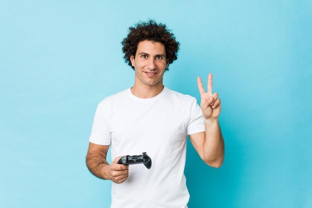 Jovem homem encaracolado caucasiano segurando um controlador de jogo mostrando o número dois com os dedos.