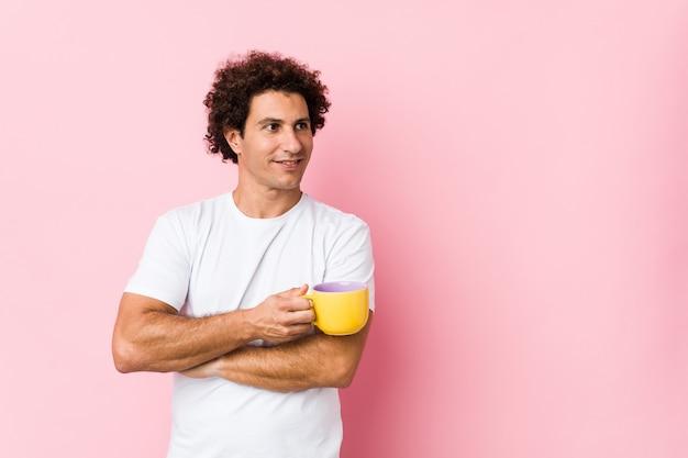 Jovem homem encaracolado caucasiano segurando um copo de chá sorrindo confiante com braços cruzados.