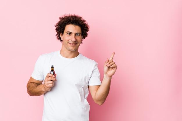 Jovem homem encaracolado caucasiano segurando um vape sorrindo alegremente apontando com o dedo indicador.