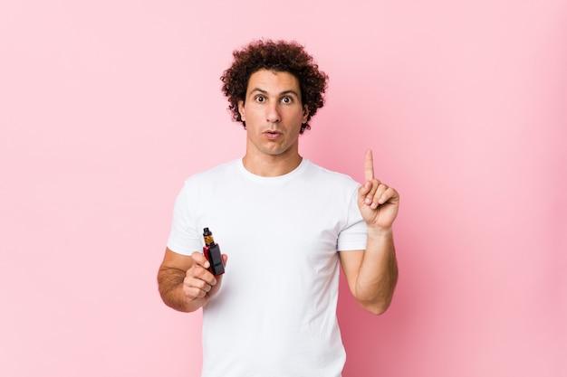 Jovem homem encaracolado caucasiano segurando um vape tendo uma ótima idéia, conceito de criatividade.