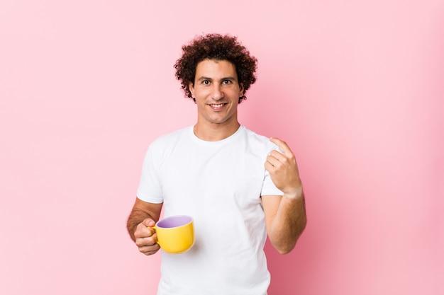 Jovem homem encaracolado caucasiano, segurando uma xícara de chá, apontando com o dedo para você, como se estivesse convidando para se aproximar.