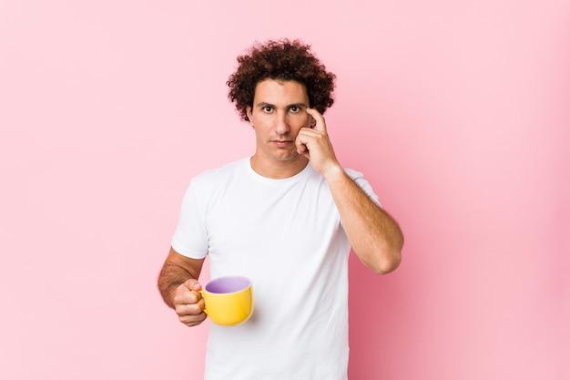 Jovem homem encaracolado caucasiano, segurando uma xícara de chá, apontando seu templo com o dedo, pensando, focado em uma tarefa.