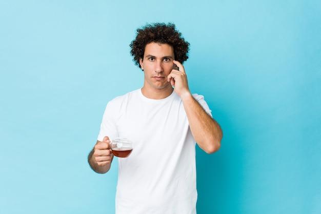 Jovem homem encaracolado caucasiano segurando uma xícara de chá, apontando sua têmpora com o dedo, pensando, focada em uma tarefa.