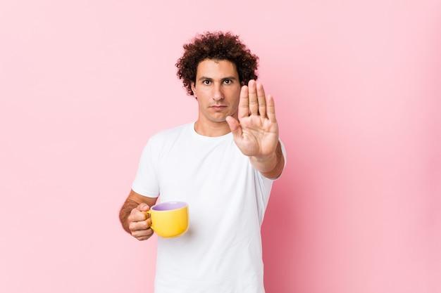 Jovem homem encaracolado caucasiano, segurando uma xícara de chá em pé com a mão estendida, mostrando o sinal de stop, impedindo-o.