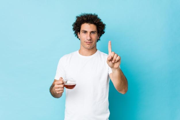 Jovem homem encaracolado caucasiano, segurando uma xícara de chá, mostrando o número um com o dedo.