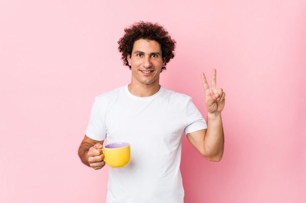 Jovem homem encaracolado caucasiano, segurando uma xícara de chá, mostrando sinal de vitória e sorrindo amplamente.