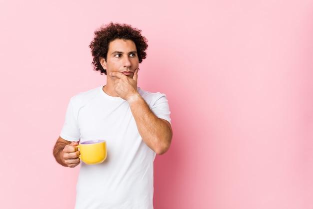Jovem homem encaracolado caucasiano, segurando uma xícara de chá, olhando de soslaio com expressão duvidosa e cética.