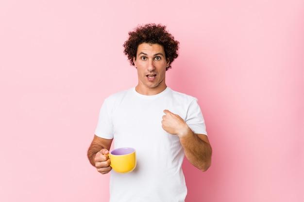 Jovem homem encaracolado caucasiano segurando uma xícara de chá surpreendeu apontando para si mesmo, sorrindo amplamente.