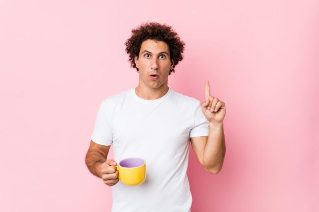 Jovem homem encaracolado caucasiano, segurando uma xícara de chá, tendo uma ótima idéia, conceito de criatividade.