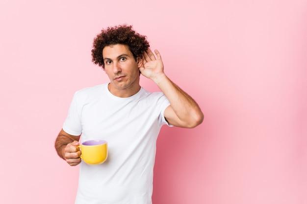 Jovem homem encaracolado caucasiano, segurando uma xícara de chá, tentando ouvir uma fofoca.