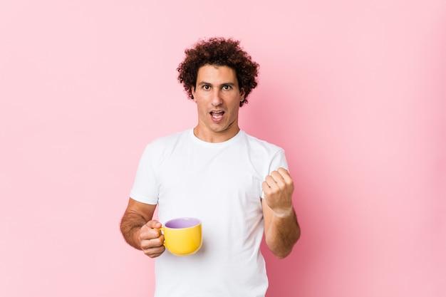 Jovem homem encaracolado caucasiano segurando uma xícara de chá torcendo despreocupado e animado. conceito de vitória