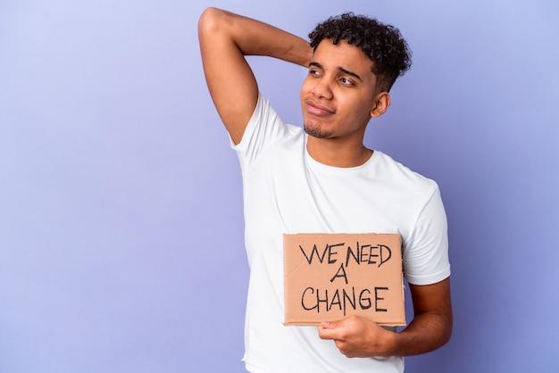 Jovem homem encaracolado isolado segurando um papelão, precisamos de uma mudança tocando a nuca, pensando e fazendo uma escolha