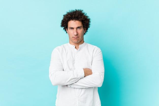 Jovem homem encaracolado maduro, vestindo uma camisa elegante infeliz com expressão sarcástica.