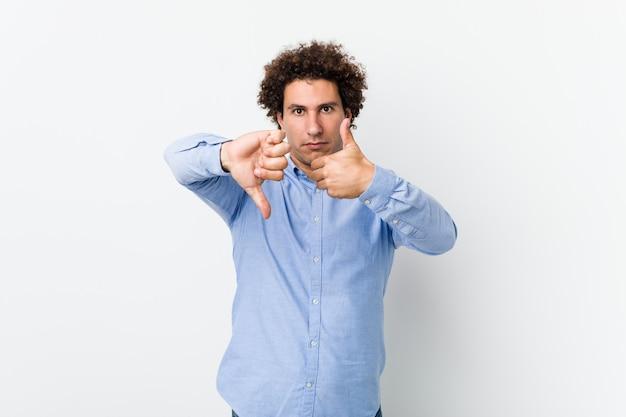 Jovem homem encaracolado maduro, vestindo uma camisa elegante, mostrando os polegares para cima e os polegares para baixo