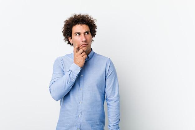 Jovem homem encaracolado maduro, vestindo uma camisa elegante, olhando de soslaio com expressão duvidosa e cética.