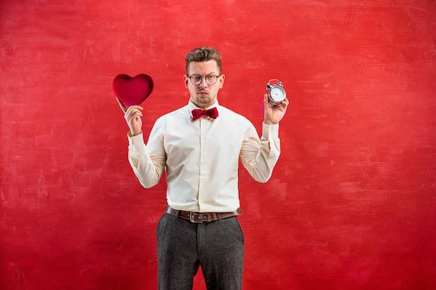 Jovem homem engraçado com coração abstrato e relógio