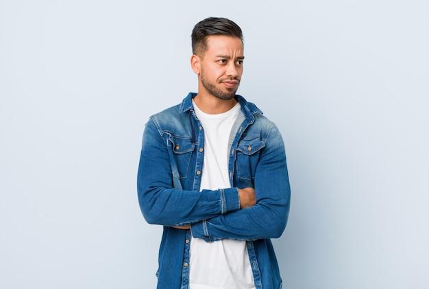 Jovem homem filipino bonito confuso, sente-se duvidoso e inseguro.