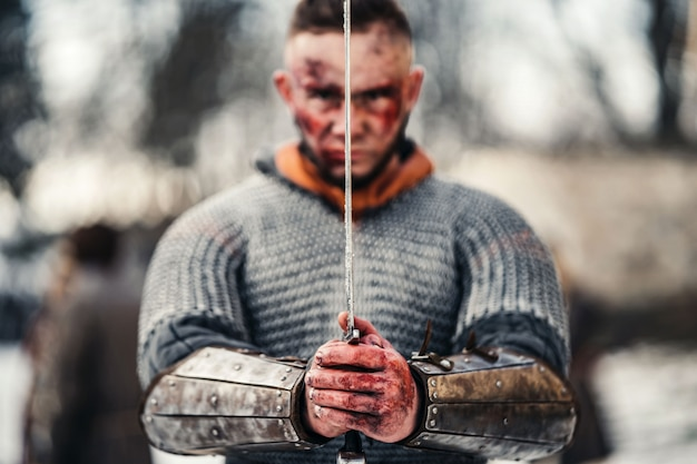 Jovem homem forte em uma fantasia de guerreiro medieval tem uma espada nas mãos bem na frente do rosto. conceito de guerra e história