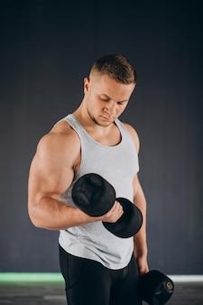 Jovem homem forte se exercitando na academia