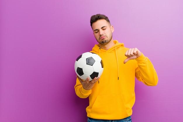Jovem homem hispânico com uma bola de futebol contra fundo roxo