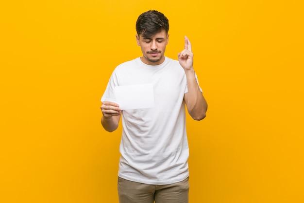 Jovem homem hispânico, segurando um cartaz cruzando os dedos por ter sorte