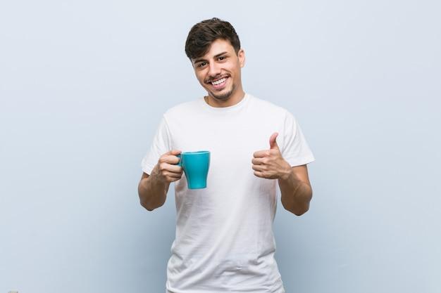 Jovem, homem hispânico, segurando um copo, sorrindo, e, levantando polegar