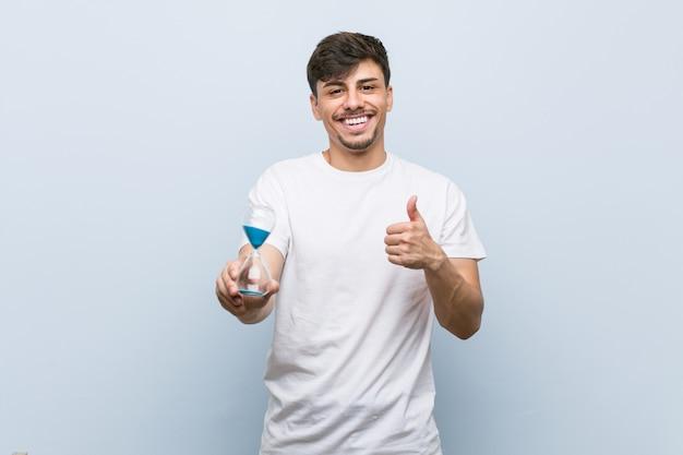 Jovem, homem hispânico, segurando uma ampulheta, sorrindo, e, levantando polegar