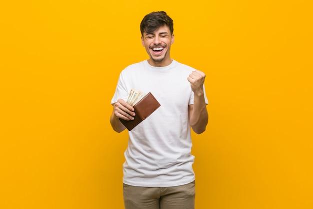 Jovem homem hispânico, segurando uma carteira torcendo despreocupado e animado