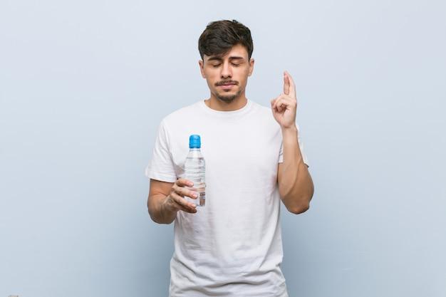 Jovem homem hispânico, segurando uma garrafa de água, cruzando os dedos por ter sorte