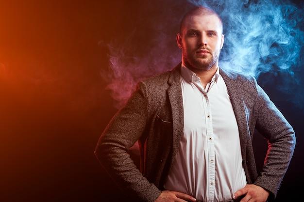 Jovem homem inteligente de camisa branca e terno cinza olhando de perto e posando contra uma fumaça vermelha