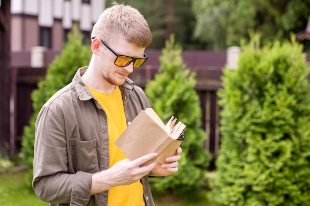 Jovem homem inteligente relaxando na natureza lendo livro, estudante do sexo masculino ao ar livre no parque com o livro de papel, tempo de refrigeração de descanso. verão, lazer, educação, estudo, conceito de passatempo. copie o espaço do texto