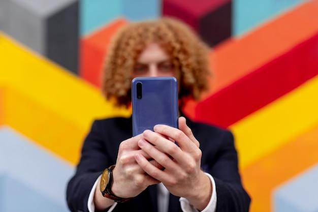 Jovem homem irreconhecível com cabelo ruivo cacheado em um terno elegante, tirando uma selfie no smartphone em pé perto de uma parede geométrica colorida na rua da cidade