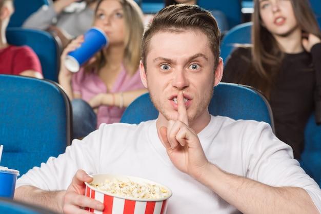 Jovem homem irritado, fazendo o gesto de silêncio olhando com raiva para a câmera no cinema