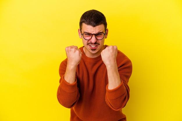 Jovem homem legal caucasiano isolado em amarelo chateado, gritando com as mãos tensas.