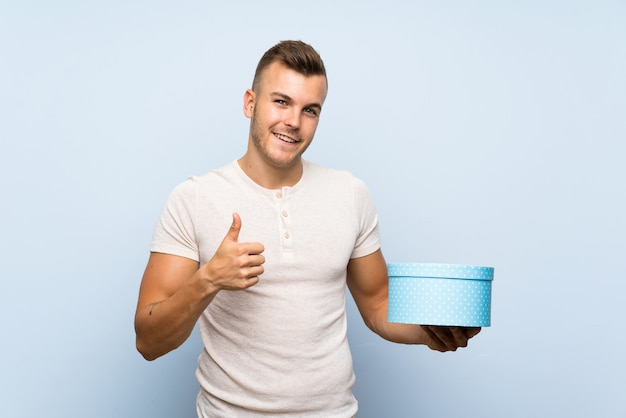 Jovem homem loiro bonito sobre parede azul isolada, segurando a caixa de presente