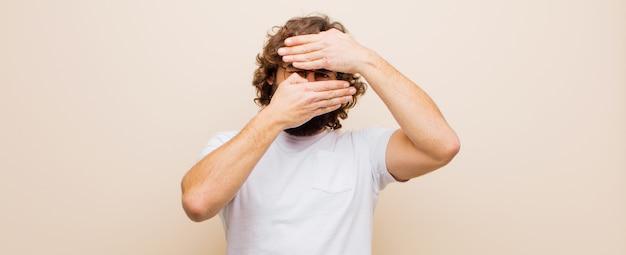 Jovem homem louco barbudo, cobrindo o rosto com as duas mãos, dizendo não à câmera! recusando fotos ou proibindo fotos contra a parede rosa