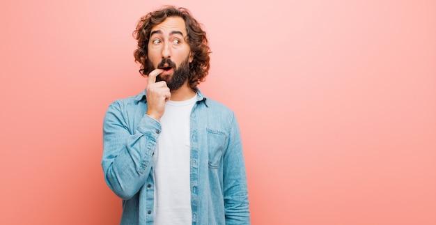 Jovem homem louco barbudo com olhar surpreso, nervoso, preocupado ou assustado, olhando para o lado em direção ao espaço da cópia contra a parede de cor lisa