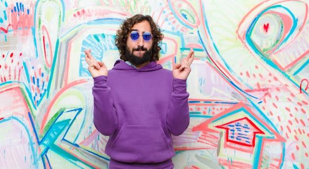Jovem homem louco barbudo cruzando os dedos ansiosamente e esperando a boa sorte com um olhar preocupado contra a parede do graffiti
