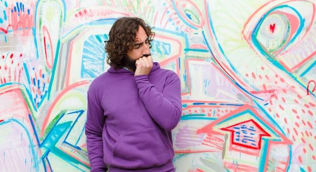 Jovem homem louco barbudo se sentindo sério, pensativo e preocupado, olhando de soslaio com a mão pressionada contra o queixo contra a parede do graffiti