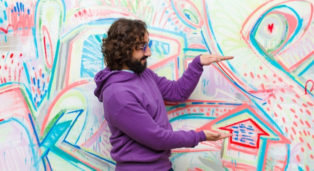 Jovem homem louco barbudo segurando um objeto com as duas mãos no espaço lateral da cópia, mostrando, oferecendo ou anunciando um objeto na parede de graffiti
