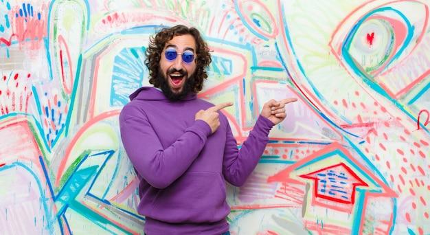 Jovem homem louco barbudo, sentindo-se alegre e surpreso, sorrindo com uma expressão chocada e apontando para o lado na parede de graffiti
