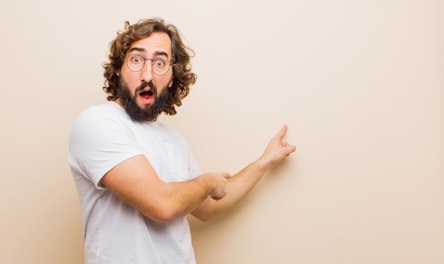 Jovem homem louco barbudo, sentindo-se chocado e surpreso, apontando para copiar o espaço ao lado com olhar espantado e de boca aberta contra a parede rosa