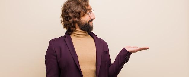 Jovem homem louco barbudo, sentindo-se feliz e sorrindo casualmente, olhando para um objeto ou conceito realizado na mão do lado contra a parede rosa