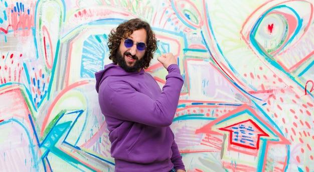 Jovem homem louco barbudo, sentindo-se feliz, satisfeito e poderoso, flexionando o ajuste e o bíceps muscular, olhando forte após o ginásio na parede de graffiti
