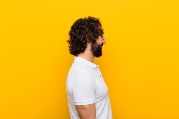 Jovem homem louco na vista de perfil, olhando para copiar o espaço à frente, pensando, imaginando ou sonhando acordado contra a parede amarela